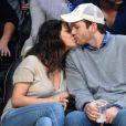 Mila Kunis et son fiancé Ashton Kutcher très amoureux et très complices au match de basket des Lakers, le 19 décembre 2014.