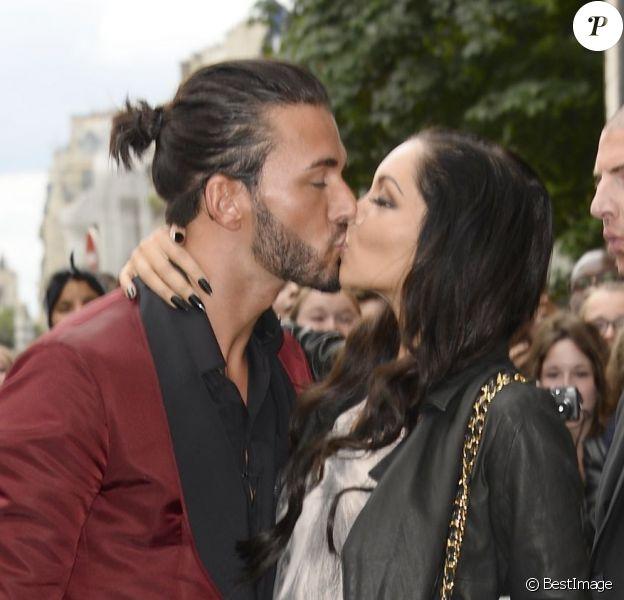 Nabilla et Thomas, stars de l'émission Les Anges de la Télé-Réalité 5, s'embrassent à l'entrée de l'atelier de Jean-Paul Gaultier. Paris, le 3 juillet 2013.