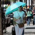 Anne Hathaway se protège du soleil avec un parapluie dans la rue à New York, le 29 avril 2015.