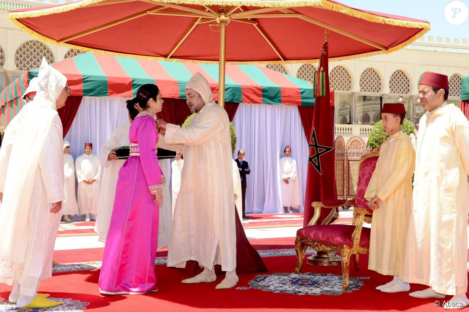 Le roi Mohammed VI du Maroc remettant les ouissams royaux, sous l'oeil de son fils le prince héritier Moulay El Hassan et de son frère le prince Moulay Rachi, le 30 juillet 2015 au palais royal, à Rabat, pour la Fête du Trône à l'occasion du 16e anniversaire de son règne.