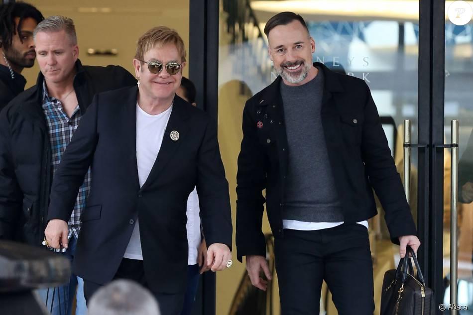 """Elton John et son mari David Furnish font du shopping chez """"Barney's New York"""" à Beverly Hills le 22 décembre 2015."""