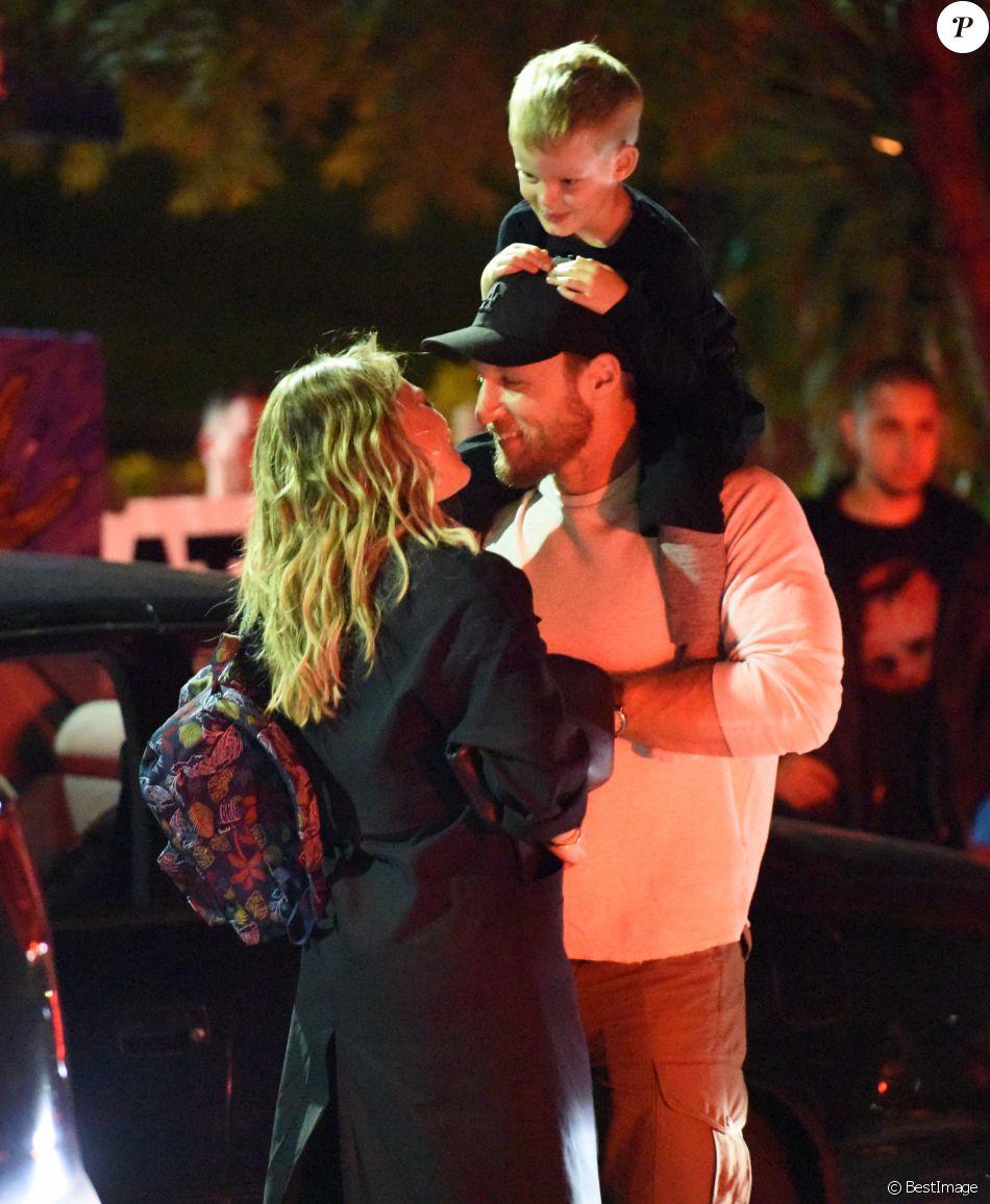 Exclusif - Hilary Duff embrasse son compagnon Jason Walsh (qui porte son fils Luca sur ses épaules!) à la sortie d'un marché à Los Angeles, le 31 octobre 2016.