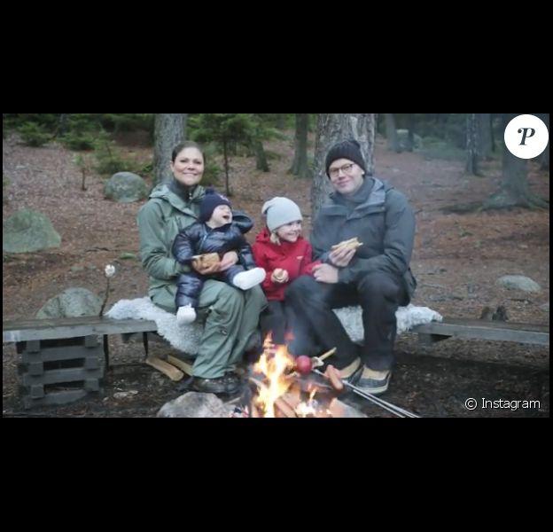La princesse Victoria et le prince Daniel de Suède avec leurs enfants la princesse Estelle et le prince Daniel autour d'un feu de camp dans le Parc national de Tyresta, au sud de Stockholm, pour souhaiter un joyeux Noël à leurs compatriotes, en décembre 2016. Image issue d'une courte vidéo partagée par la cour royale de Suède sur son compte Instagram.