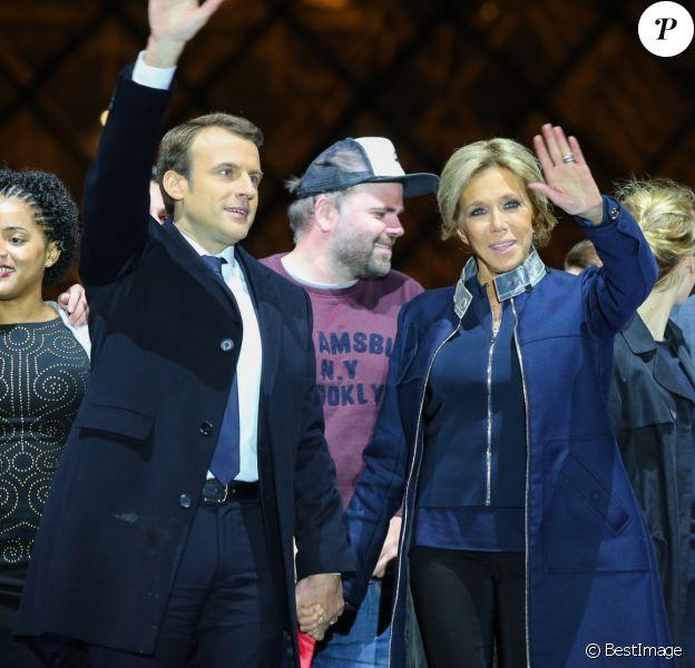 Emmanuel Macron, élu président de la république, et sa femme Brigitte Macron (Trogneux), saluent les militants devant la pyramide au musée du Louvre à Paris, après sa victoire lors du deuxième tour de l'élection présidentielle. Le 7 mai 2017.