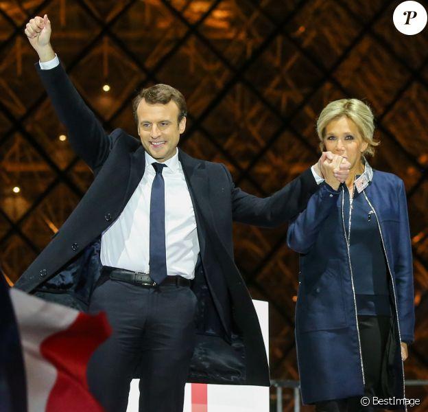Emmanuel Macron, élu président de la république, et sa femme Brigitte Macron, saluent les militants devant la pyramide au musée du Louvre à Paris, après sa victoire lors du deuxième tour de l'élection présidentielle. Le 7 mai 2017.