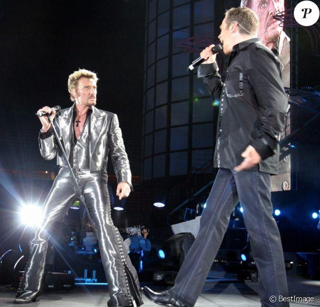 """Garou et Johnny Hallyday chantent """"Ma Gueule"""" au Parc des Princes, à Paris le 14 juin 2003."""