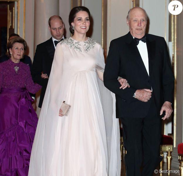La duchesse Catherine de Cambridge, enceinte et en Alexander McQueen, arrive au bras du roi Harald V de Norvège au palais royal à Oslo le 1er février 2018 pour le dîner organisé dans le cadre de sa visite officielle avec le prince William, qui suit en donnant le bras à la reine Sonja.