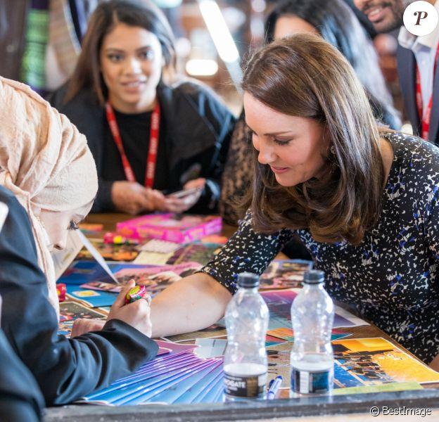 Kate Middleton, duchesse de Cambridge, enceinte, s'est fait faire un tatouage au henné par une jeune femme de l'Asian Voices Youth Project lors de sa visite du centre The Fire Station à Sunderland avec le prince William le 21 février 2018.