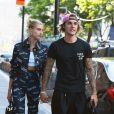 Hailey Baldwin et Justin Bieber se tiennent la main en sortant du restaurant Nobu à Los Angeles. Hailey porte un ensemble Versace, le 5 juillet 2018.