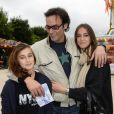 Anthony Delon et ses filles Lou et Liv lors de l'inauguration de la fête foraine des Tuileries à Paris le 28 juin 2013