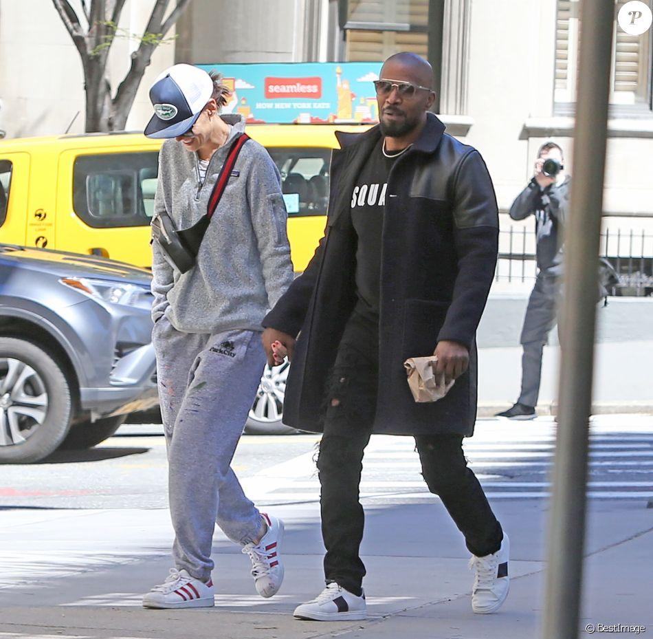 Faisant fi des nombreuses rumeurs concernant leur rupture, Katie Holmes et Jamie Foxx se promènent main dans la main et se sourient amoureusement dans les rues ensoleillées de New York. Katie porte une marinière blanche et bleue, un pantalon de jogging oversize gris, de larges lunettes de soleil, une casquette, un sac banane et une paire de baskets All Stars Adidas. Jamie porte un sweatshirt noir Dsquared2, un pantalon noir, une paire de baskets blanches, une longue veste bi-matière bleue marine et noire, une large montre dorée et une fine chaine en or ainsi que des lunettes de soleil. New York, le 16 avril 2019.