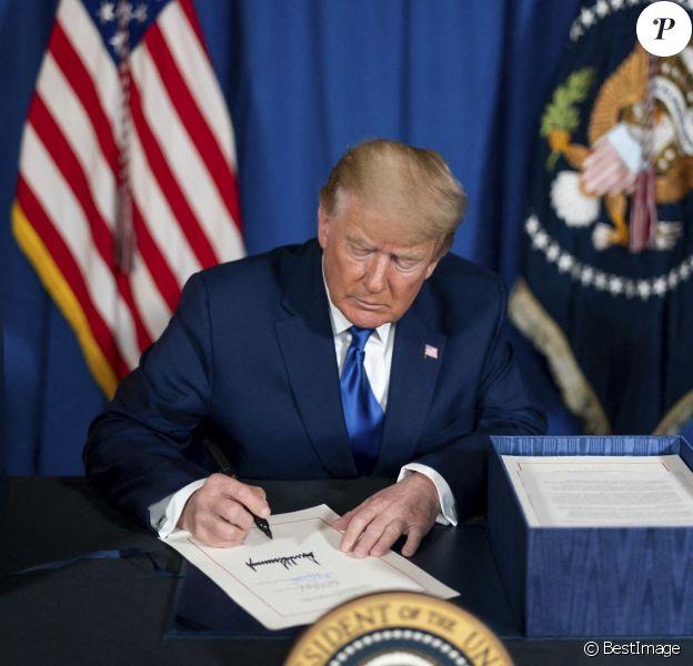 Le président américain Donald Trump, signe la loi de crédits consolidée 2021 dans le salon de thé de Mar-a-Lago à Palm Beach, en Floride.