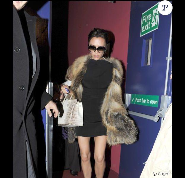 Victoria Beckham divine dans une micro robe noire rehaussée d'une veste en fourrure, et portée avec des compensées, des lunettes de soleil et un it-bag Hermès en python.