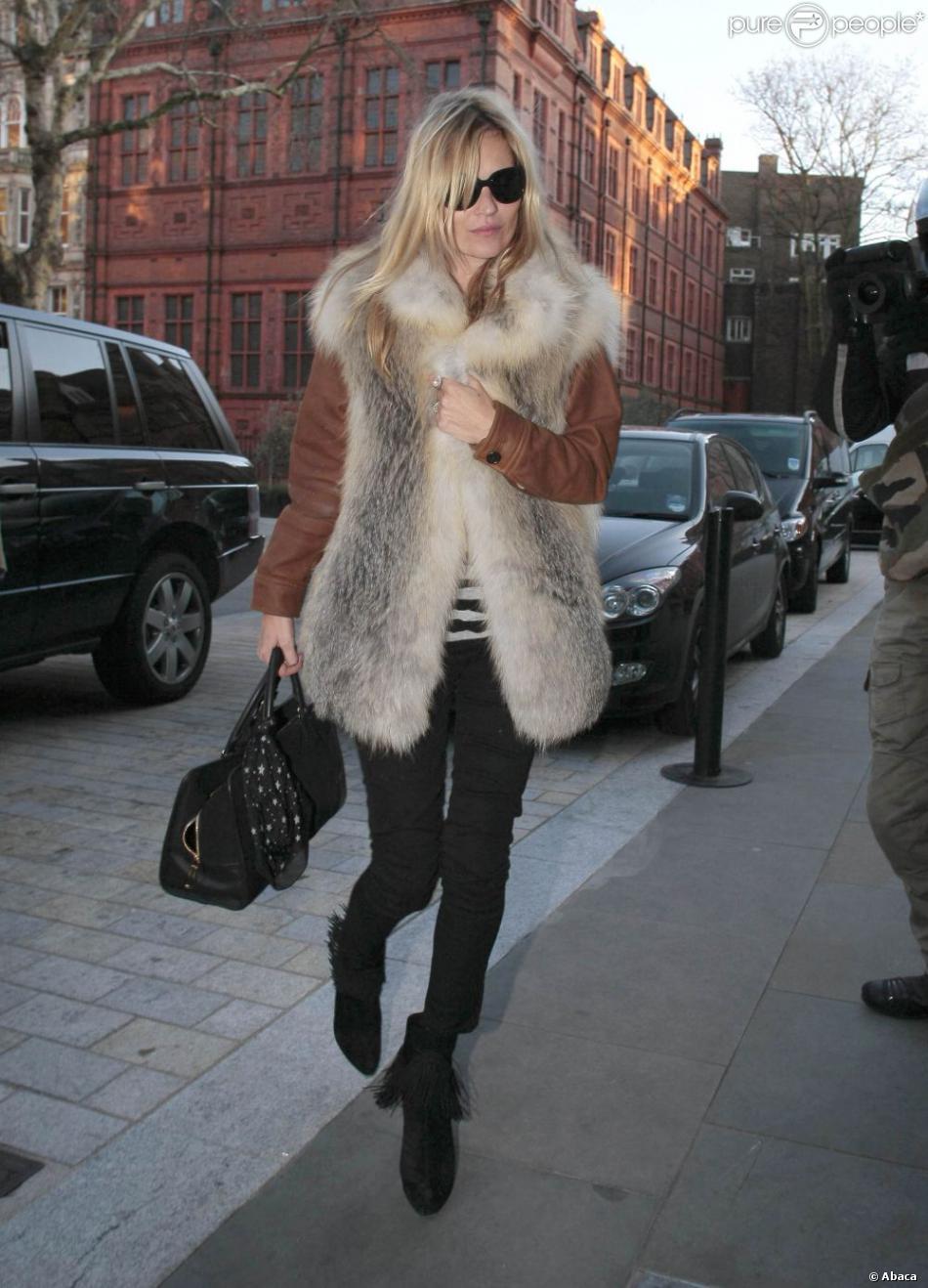 Kate Moss à Londres, lutte contre la fraîcheur ambiante grâce à une veste en fourrure, un slim noir et des bottines Christian Louboutin. Le 2 février 2012.