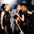 Kristen Stewart se baisse pour laisser Lily Cole faire la bise à Chris Hemsworth lors de l'avant-première du film Blanche-Neige et le chasseur à Londres le 14 mai 2012
