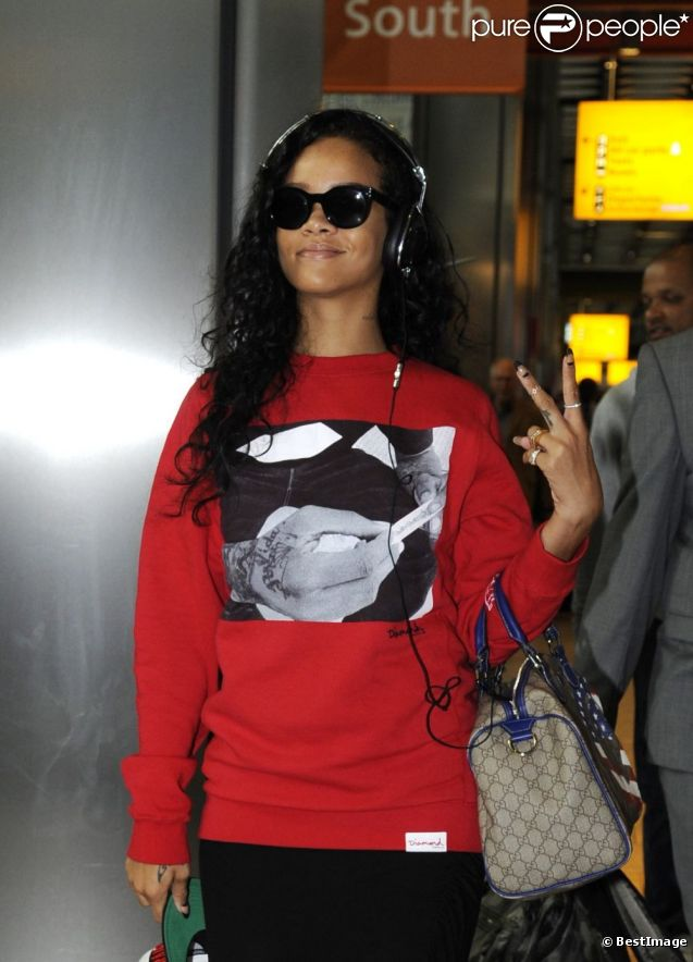 "Rihanna habillée d'un pull Diamond Supply Co., lance un ""Deuces"" aux photographes à son arrivée à l'aéroport d'Heathrow. Londres, le 27 août 2012."