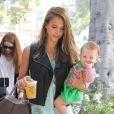 Jessica Alba, les bras chargés par son sac Tod's, une boisson et sa fille Haven, porte un chemisier vert menthe Rails, un legging Nebula de Kymerah et des sandales Surface To Air. Los Angeles, le 24 août 2012.