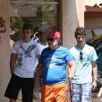 Paul-Loup Sulitzer entouré de ses fils James et Edouard au Club 55, près de Saint-Tropez, le 16 juillet 2012.