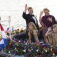 Le roi Willem-Alexander des Pays-Bas, la reine Maxima et leurs filles Catharina-Amalia et Alexia saluent le public lors de la parade aquatique précédant le banquet final de l'intronisation du fils de la princesse Beatrix, le 30 avril 2013 à Amsterdam.