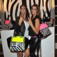 Laury Thilleman prend la pose auprès de Laurie Cholewa lors de la présentation du sac de Laury Thilleman pour la marque La Halle à Paris, le 27 juin 2013