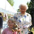 Elizabeth II posant avec la jeune Jessica Fitch et son ourson Bertie,  le 11 juillet 2013 au premier jour du Coronation Festival organisé à Buckingham Palace par la Royal Warrants Holders Association à l'occasion des 60 ans du couronnement de la reine.