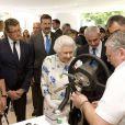 La reine Elizabeth II visitant le 11 juillet 2013 les installations du Coronation Festival organisé à Buckingham Palace à l'occasion des 60 ans de son couronnement par la Royal Warrants Holders Association.