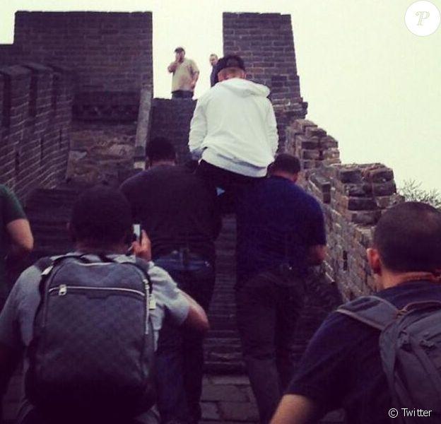 Justin Bieber se fait porter par ses gardes du corps pour aller visiter la Grande Muraille de Chine, le 30 septembre 2013.