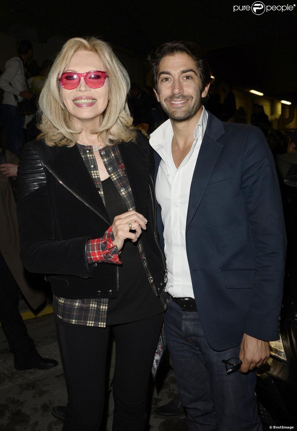 Amanda Lear et Mathieu Delarive au défilé Givenchy prêt-à-porter printemps-été 2014 lors de la Fashion Week à la Halle Freyssinet, à Paris, le 29 septembre 2013.