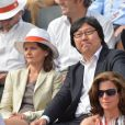 Jean-Vincent Placé et sa compagne Eva Sas assistent au quart de finale entre Rafael Nadal et Stanislas Wawrinka lors des Internationaux de France de tennis à Roland-Garros, à Paris, le 5 juin 2013.