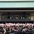 salue depuis un balcon du palais la foule venue nombreuse pour célébrer le 80e anniversaire de l'empereur, à Tokyo le 23 décembre 2013.