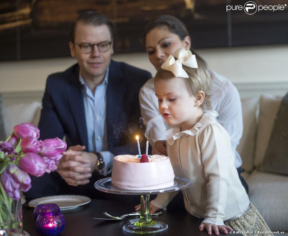 La princesse Estelle de Suède soufflant les bougies pour son 2e anniversaire, le 23 février 2014, sous le regard de ses parents la princesse Victoria et le prince Daniel.