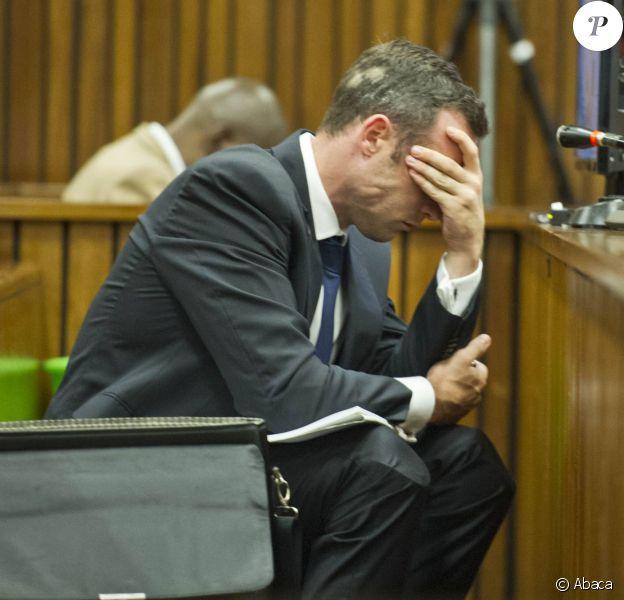Oscar Pistorius, prostré sur le banc des accusés avec son seau à ses côtés, écoute les témoins défilés à la barre durant son procès pour meurtre, le 12 mars 2014