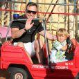 Elton John et son mari David Furnish s'amusent sur un manège avec leurs deux fils Elijah Joseph Daniel Furnish John et Zachary Jackson Levon Furnish, pendant leurs vacances en famille à Saint-Tropez. Le 22 août 2013.