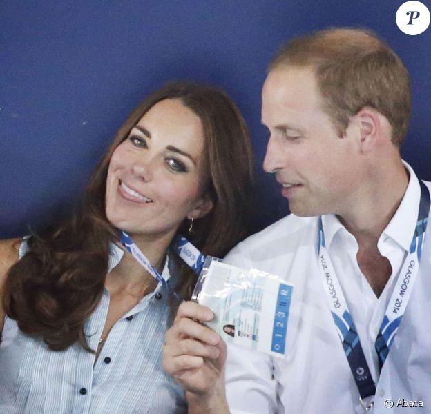Kate Middleton étranglée par le prince William, qui essaye galamment de la ventiler ! Le duc et la duchesse de Cambridge dans les gradins du Tolcross Swimming Centre de Glasgow le 28 juillet 2014 pour les épreuves de natation des XXe Jeux du Commonwealth.