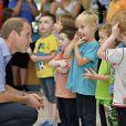 Le prince William rencontre des enfants lors d'une visite avec son frère Harry à des protagonistes du programme Coach Core en marge des XXe Jeux du Commonwealth, le 29 juillet 2014 à Glasgow.
