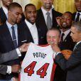 Barack Obama a reçu un maillot floqué POTUS (President Of The United States) des mains de Chris Bosh et Ray Allen, alors qu'il recevait l'équipe championne NBA du Heat de Miami à la Maison Blanche à Washington, le 14 janvier 2014