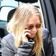Ashley Olsen, suivie de sa soeur jumelle Mary-Kate qui fume une cigarette, sort d'une voiture à New York, le 8 septembre 2014.