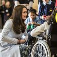 Kate Catherine Middleton, duchesse de Cambridge, enceinte discute avec Martina McDonagh, 17 ans, qui est en chaise roulante lors de l'inauguration du Kensington Leisure Centre à Londres le 19 janvier 2015. Elle porte un manteau de la marque Séraphine.  The Duchess of Cambridge talks to Martina McDonagh aged 17 as she sits in her wheelchair. The Duchess is touching he stomach and describing how she can feel her baby kick. The Duchess was formally opening new Kensington leisure centre in London on January 19, 2015. The Duchess of Cambridge formally opened the Kensington Leisure Centre by touring ethe facilities, including the swimming pool, gym and sauna and watchd groups of children from nearby Primary Schools in the Main Sports Hall playing various sports.19/01/2015 - Londres