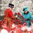 La reine Elizabeth II découvrant le 16 octobre 2014 l'installation  Blood Swept Lands and Seas of Red de Paul Cummins à la Tour de Londres pour le centenaire de la Première Guerre mondiale.