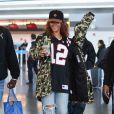 """""""Rihanna à l'aéroport JFK de New York, porte une vasquette et une doudoune Puma (collection Bape FC de Bape et Puma), un maillot de football des Atlanta Falcons, un jean et des chaussures Prada. Le 1er mai 2015."""""""