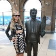 Paris Hilton arrive à la gare de Liverpool, le 13 mai 2015. Elle prend le temps de poser avec ses fans et avec une statue !. Elle est à Liverpool pour aller fêter le premier anniversaire de son parfum au Superdrug.