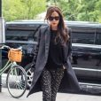 Victoria Beckham à New York, porte un manteau, un pull et une pochette noirs (manteau et pochette Victoria Beckham), un pantalon à motifs floraux Victoria Beckham et des chaussures Casadei. Le 4 juin 2015.