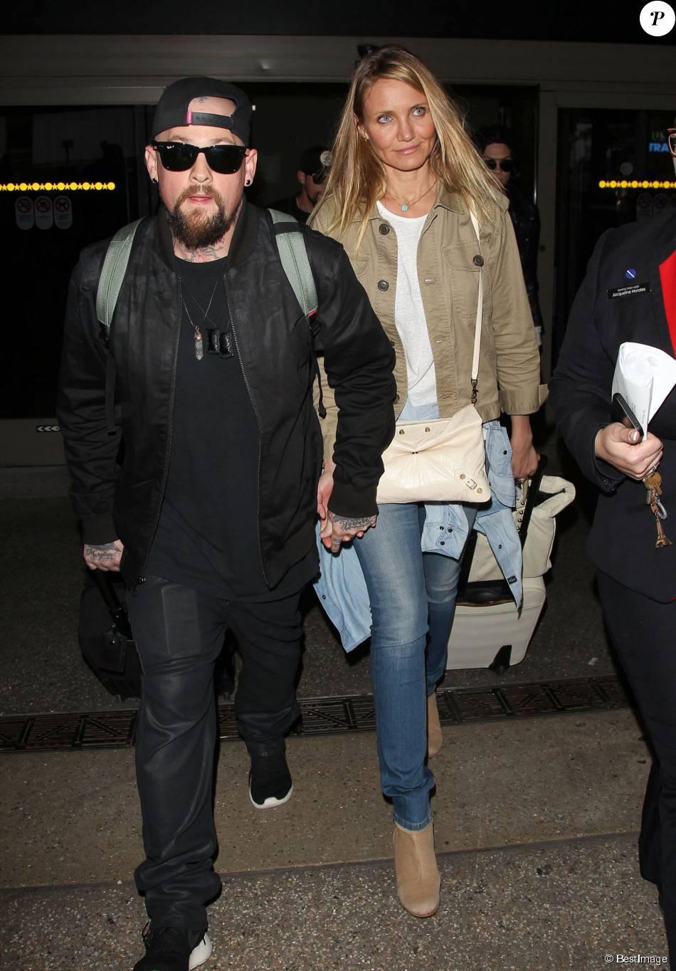 Cameron Diaz et son mari Benji Madden lors de leur arrivée à l'aéroport LAX de Los Angeles, le 31 août 2015. Cameron Diaz dissimulerait son ventre pour couvrir une supposée grossesse...