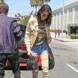 """Kendall Jenner arrive au restaurant """"Il Pastaio"""" à Beverly Hills, habillée d'une chemise dorée à broderies, d'un mini-short vintage Levi's (retravaillé par RE/DONE) et de bottes Balmain (collection automne 2016). Des lunettes de soleil Ray-Ban et un sac Givenchy (modèle Lucrezia) complètent sa tenue. Le 13 juin 2016."""