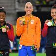 Sanne Wevers sur la plus haute marche du podium entre les Américaines Simon Biles (bronze) et Lauren Hernandez (argent) le 15 août 2016 après avoir remporté le concours de la poutre en gymnastique artistique aux Jeux olympiques de Rio de Janeiro. Une première historique pour les Pays-Bas, sous les yeux de sa soeur jumelle Lieke, qui fait aussi partie de l'équipe néerlandaise.