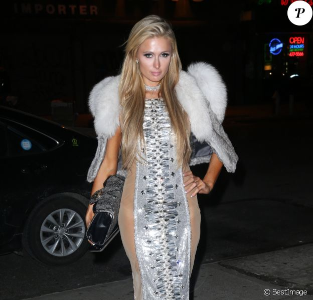 Paris Hilton porte une robe très sexy et transparente dans les rues de New York, le 14 février 2017  Celebrity socialite Paris Hilton showed some skin in a long, silver dress with see through sides as she headed out in New York City, New York on February 14, 201714/02/2017 - New York