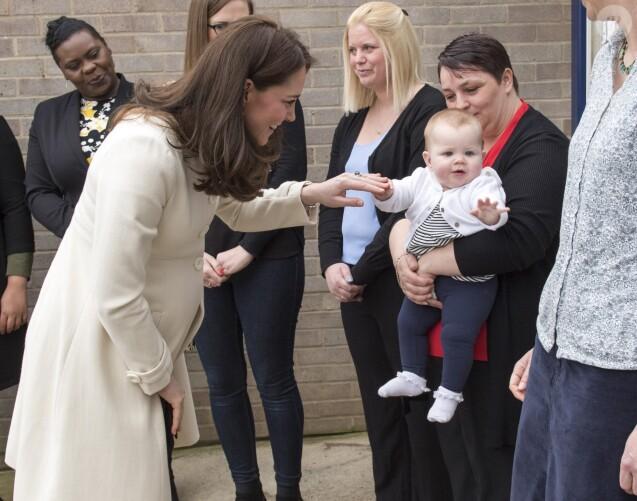 La duchesse Catherine de Cambridge, enceinte de huit mois et vêtue d'un manteau Jojo Maman Bébé, amuse un bébé le 6 mars 2018 lors de sa visite à l'école primaire Pegasus à Oxford pour y observer le travail de l'association Family Links UK.