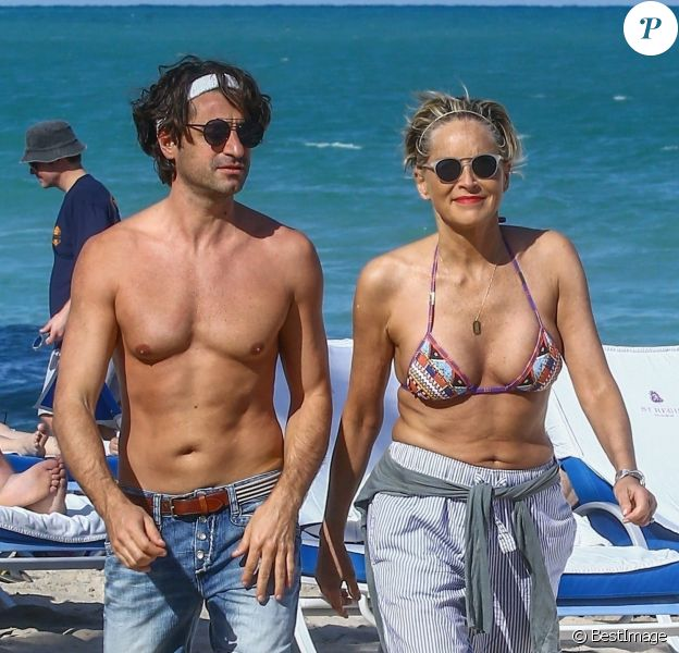 Sharon Stone profite de sa journée avec son nouveau compagnon sur une plage de Miami à la veille des ses 60 ans q'elle fêtera le 10 mars; Miami le 9 mars 2018.  Sharon Stone looked far from single on Thursday as she packed on the PDA with a younger man in Miami and even showed off a diamond ring on her wedding finger. The 59-year-old actress who celebrates her birthday on Saturday, looked incredible in a tiny bikini and striped pants. Miami March 9, 2018.09/03/2018 - Miami
