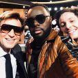 """Laurent Delahousse, portant des lunettes de soleil, partage un selfie avec Maître Gims et Vianney sur le plateau de """"20h30 le dimanche"""" sur France 2 le 1er avril 2018."""