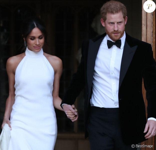"""Le prince Harry, duc de Sussex, et Meghan Markle, duchesse de Sussex quittent le château de Windsor à bord d'une Jaguar Type E cabriolet en tenue de soirée après leur cérémonie de mariage, pour se rendre à la réception à """"Frogmore House"""" à Windsor le 19 mai 2018."""